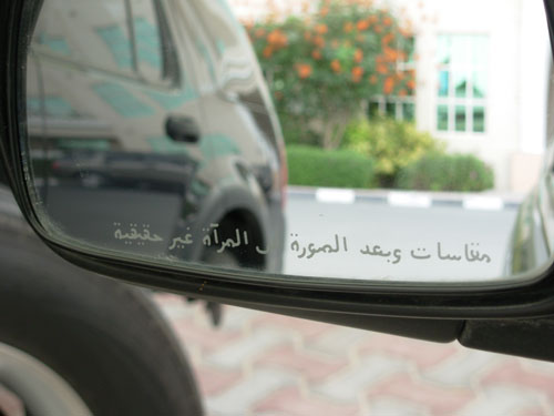 Photo of our Toyota Echo with arabic writing on the mirrors saying Objects in Mirror Are Closer Than They Appear